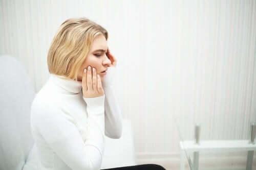 Kvinde med tandpine tager sig til kind