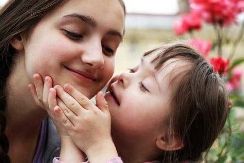 Barn med Downs syndrom kysser sin mor