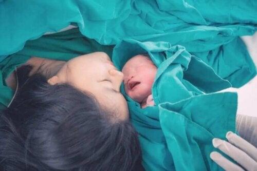 Nyfødt baby med sin mor, der har oplevet bristning under fødsel
