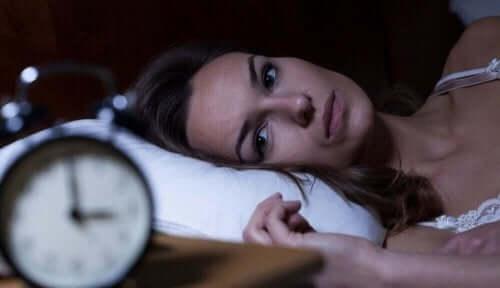 Kvinde ligger søvnløs i seng