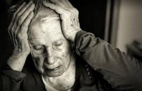 Ældre kvinde, der tager sig til hoved, oplever effekten af mangel på cholin i forebyggelse og behandling af kognitiv sygdom som Alzheimers