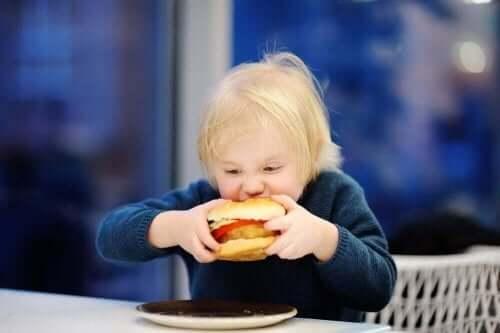 Barn med stor burger symboliserer overvægt i barndommen