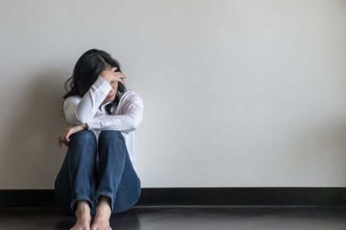 Kvinde sidder på gulv og skjuler ansigt bag sin hånd