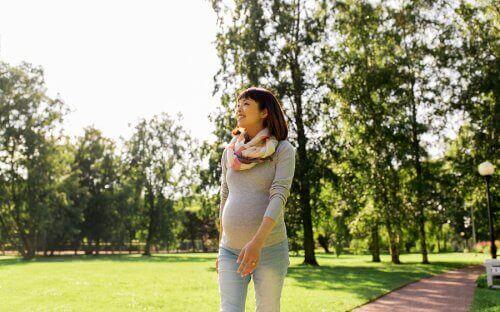 Gravid kvinde går tur som eksempel på motion under graviditet