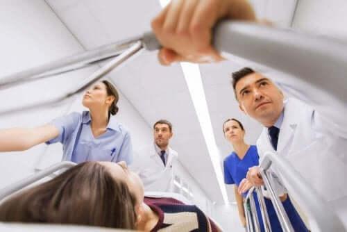 Kvinde i seng køres af læger