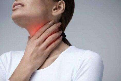 Kvinde tager sig til halsen, som er rød