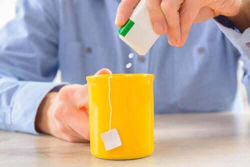 Mand hælder sødemiddel i en kop te