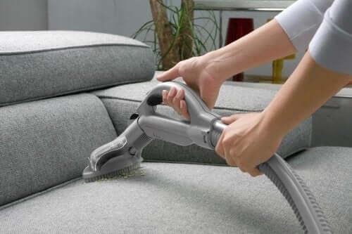 Kvinde støvsuger sofa