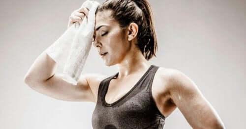 Kvinde i træningstøj tørrer sin pande