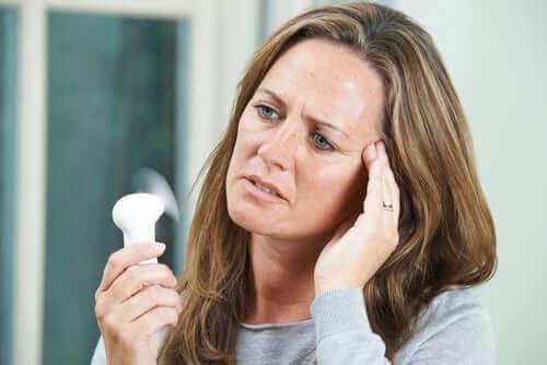 Kvinde med vifte oplever hedeture i overgangsalderen