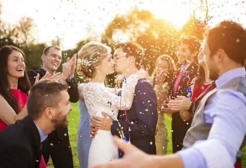 Brudepiger og brudesvende står med de andre gæster rundt om det kyssende brudepar