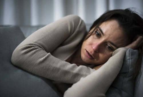 Grædende kvinde på sofa har brug for snacks mod depression