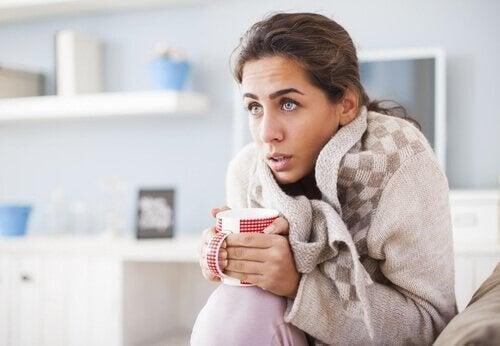 Kvinde forsøger at få varmen med varm te og varmt tøj