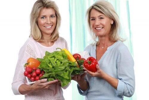 To kvinder holder en masse grøntsager