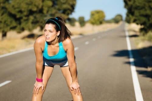 Kvinde, der stopper op på løbetur, tænker over sammenhængen mellem mælkesyre og motion