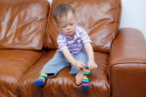 Udvikling af motorisk færdighed: Et barn, der tager sokker på