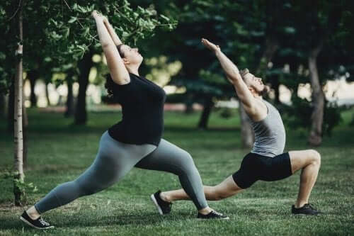 En mand og en kvinde, der strækker sig i parken for at sænke kolesterol uden statiner