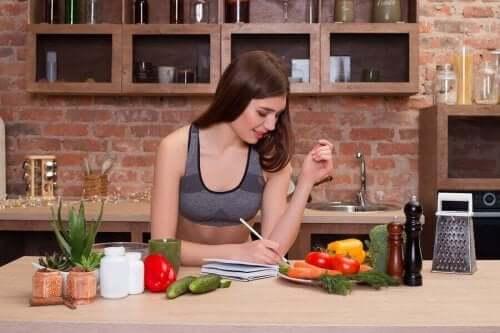 En kvinde, der skriver ved et køkkenbord