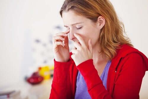 En kvinde, der holder sig for næsen i smerte