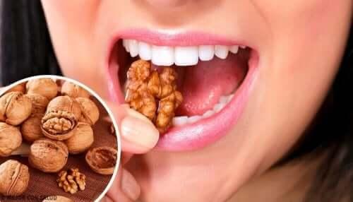Kvinde spiser valnødder, der indeholder omega-3 fedtsyrer