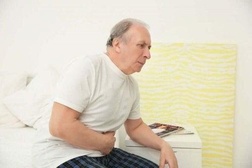 Ældre mand sidder på kanten af sengen med smerter