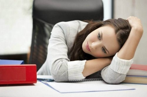 Depressiv dame ved bord med notesbog