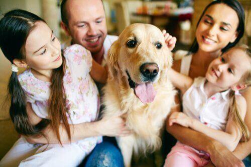 Familie sidder med en hund
