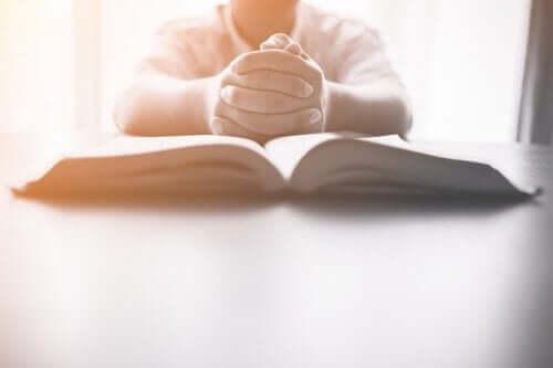 Barn med foldede hænder foran åben bog