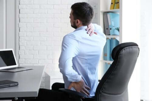 Mand strækker ud på kontorstol for at behandle lændesmerter