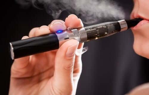 Kvinde damper på en e-cigaret
