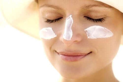 Kvinde anvender solcreme som en del af foryngelse af huden