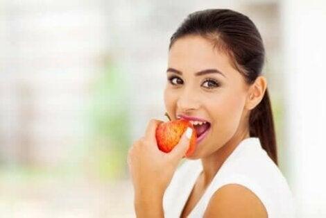 Kvinde spiser et æble, der indeholder pektin
