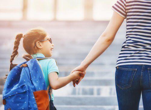 Mor med datter med skoletaske på
