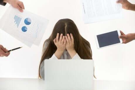 Kvinde, der skjuler ansigt bag hænder, peges fingre af på kontor