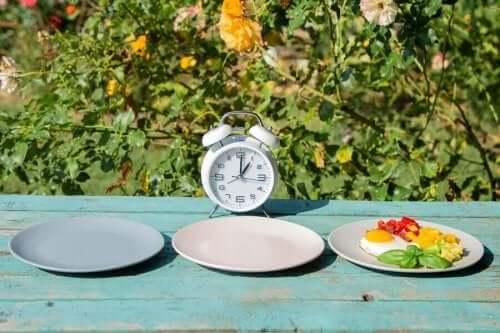 Tallerkener foran ur symboliserer fem måltider om dagen
