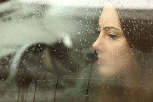 Kvinde ser ud af regnfyldt vindue