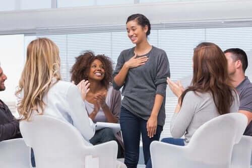 Pige står som midtpunkt for gruppe af klappende personer