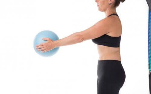 Kvinde med bold dyrker pilates under graviditet