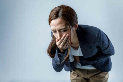 Kvinde hoser og tager sig til mund og mave