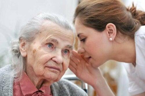 Kvinde hvisker til ældre kvinde med høretab