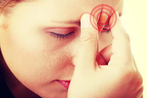 Person, der tager sig til pande, oplever hostehovedpine