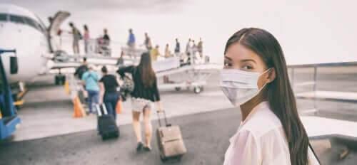 Kvinde med mundbind er ved at stige ombord på et fly
