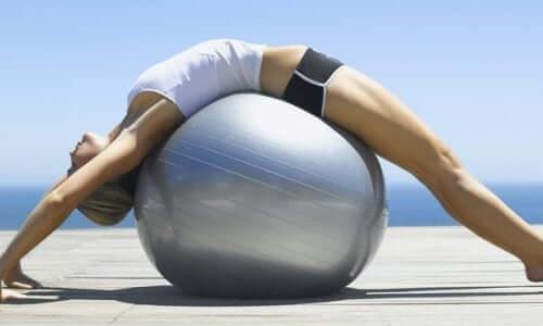 Kvinde på stor bold dyrker pilates