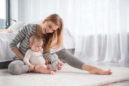 Mor leger med baby på gulv