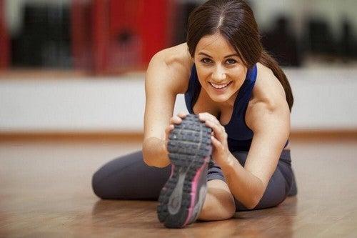Kvinde laver strækøvelser på gulvet