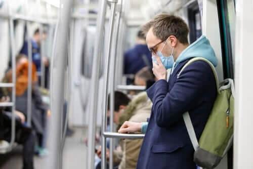 Mand har mundbind på i metroen