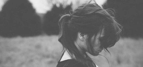 Sort/hvid billede af nedtrykt kvinde , der har problemer med at tilgive sig selv