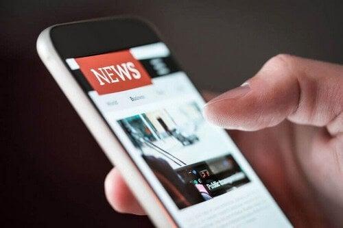 Person læser nyheder på sin telefon