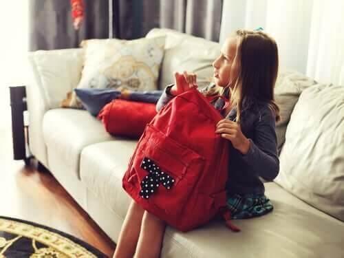 Der er et forhold mellem skoletasker og rygsmerter, som illustreres af pige, der sidder med skoletaske