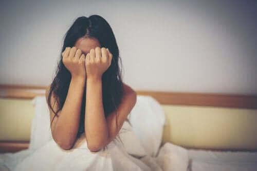 Pige skjuler ansigt bag hænder som følge af børnemobning